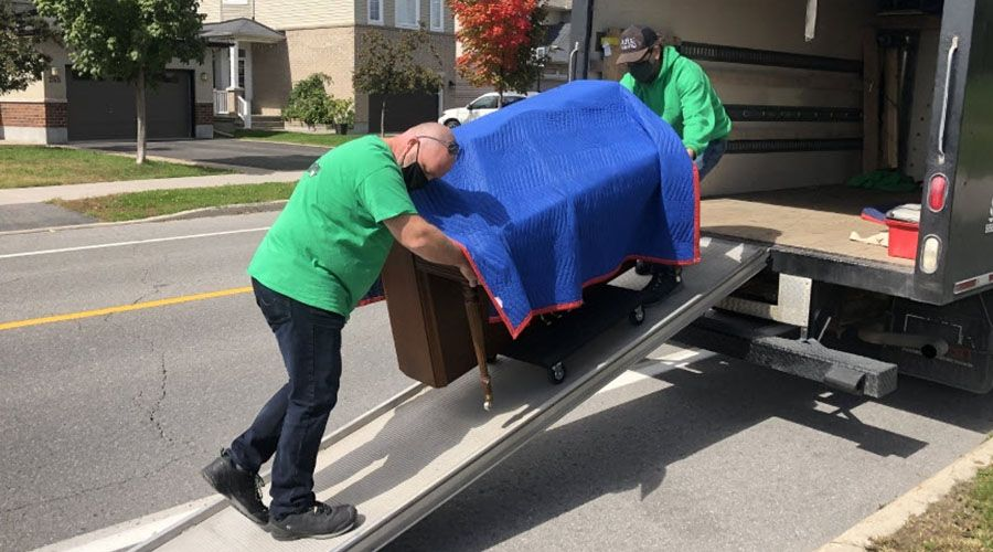 men loading a piano into a delivery truck